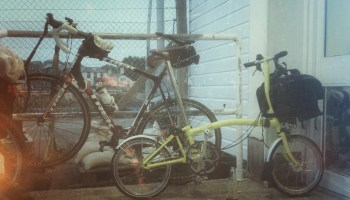 Yellow fold-up bike parked in front of full-size road machine