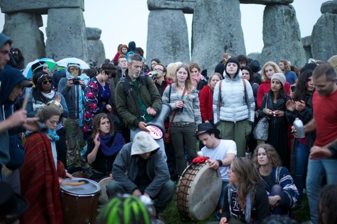 An eclectic band plays a range of percussion instruments in front of the stones