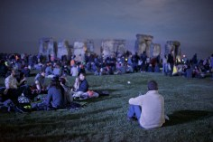 A lone figure sits on a hill watching the crowd around the stones from a distance