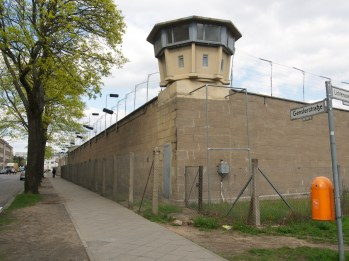 A concrete watchtower stands behind a concrete wall on the corner of a residential street