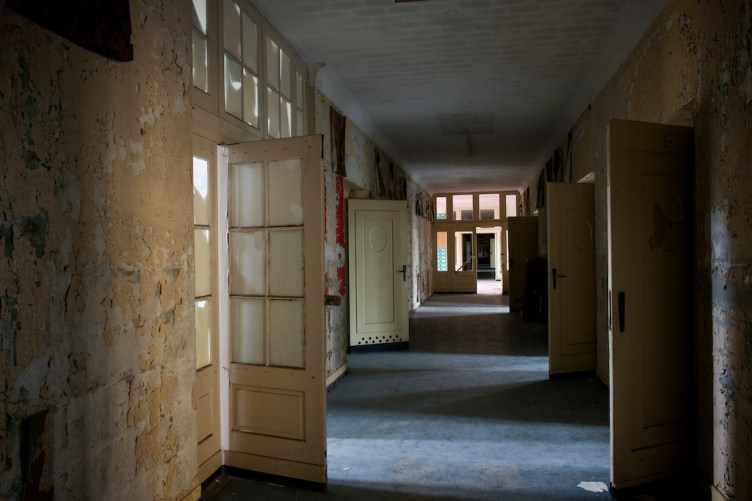 Traditional urbex shot showing forlorn doors opening onto paint-peeling corridor