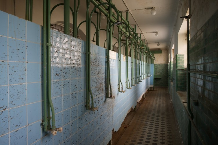 A row of bare headless showers mounted onto a cold tiled wall, splattered with unspeakable brown liquid