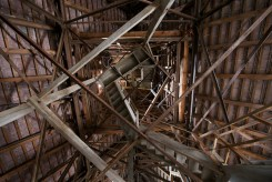 Inside the bell tower, a rickety wooden staircase-cum-ladder climbs out of view