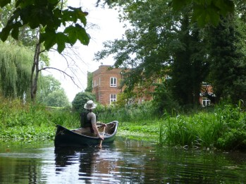 A lone canoe approaches large house and gardens on Abbey River, Chertsey