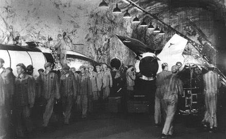 Small black and white photo showing concentration camp prisoners working on a rocket in a tunnel