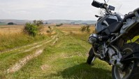 Motorcycle parked at the start of a rutted trail in rural England