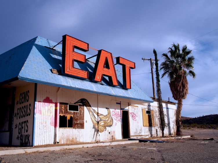A dilapidated restaurant bearing the legend EAT in huge letters on its roof now only serves graffiti chicken