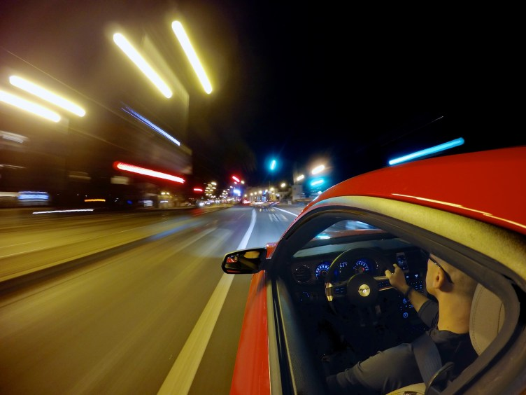 Semi-long exposure with camera clamped to the side of a red car as it drives down a darkened city road