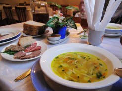 A table spread with some luminous soup, assorted cuts of meat, bread, and a jar of dark liquid