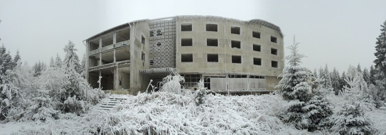 Panoramic view of the exterior of a derelict hotel, broken windows looking out over frozen grounds in the middle of winter