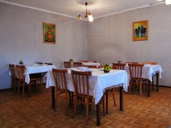 Four tables laid for dinner in a small room, basically furnished with two paintings and semi-functional light fitting
