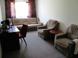 A small room containing a desk, chair, and three piece suite of uncertain vintage
