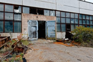Blue double doors open to reveal a dark factory hall