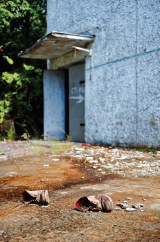 A pair of worn leather boots rest on concrete floor outside an open door at the edge of a derelict building