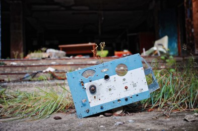 The blue facia of some kind of radio box rests in weeds, entrance to a large building behind.