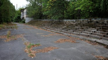 A long line of concrete steps serve as seats at the edge of the athletics stadium