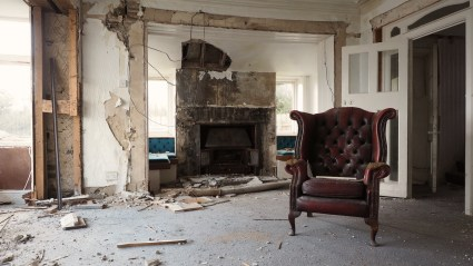 Interior picture of a lounge, complete with leather chair and smashed fireplace