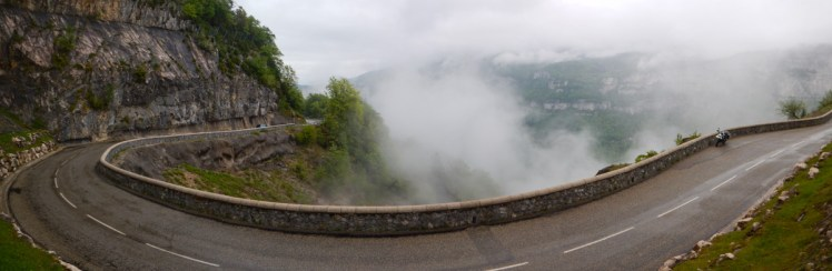 Wide shot of bike parked in middle of sweeping mountain corner, a cloud trying to eat the apex