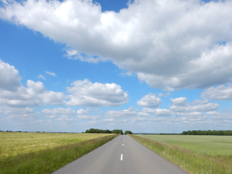 Dead straight road leading into the distance under a blue and white sky