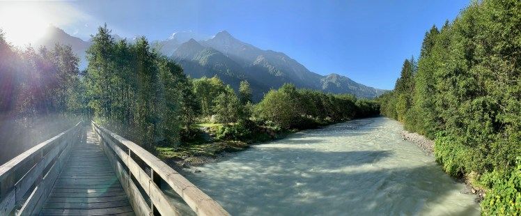 Panoramic shot of a wooden footbridge across alpine stream