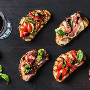 Brushetta snacks for wine. Variety of small sandwiches on dark rustic wooden backdrop, top view