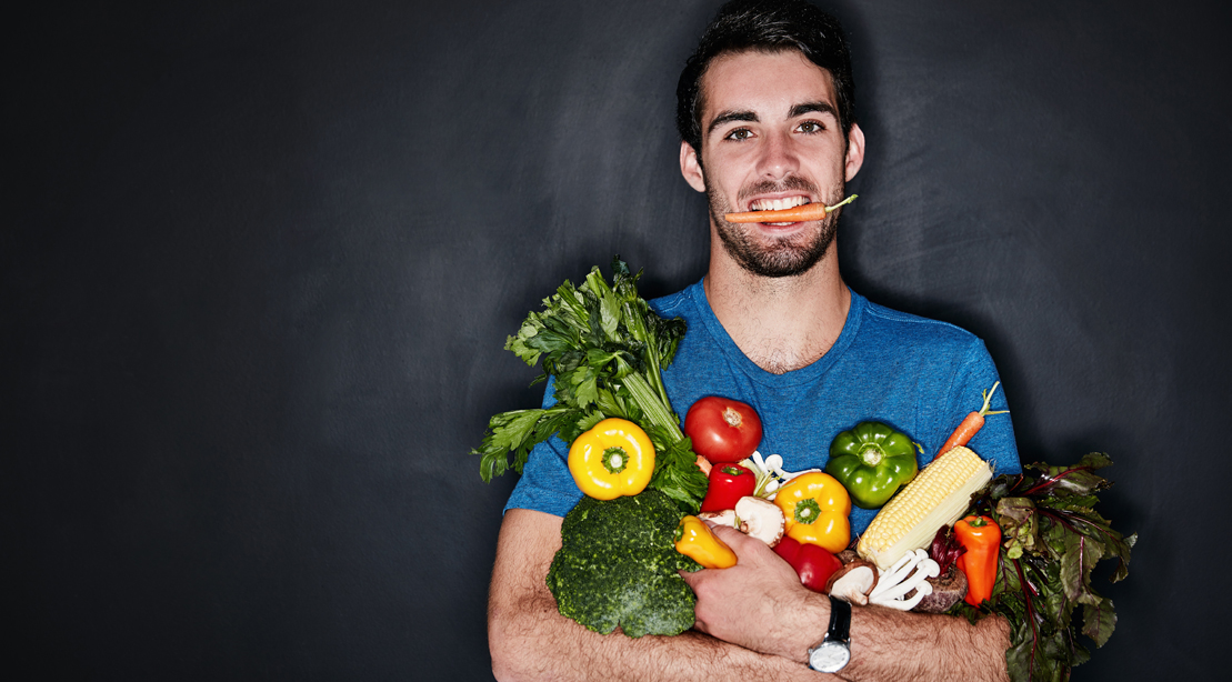 Man holding a carrot in his mouth while holding a bag of vegetable and produce