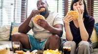 Overweight interracial couple eating unhealthy junk food that causes inflammation