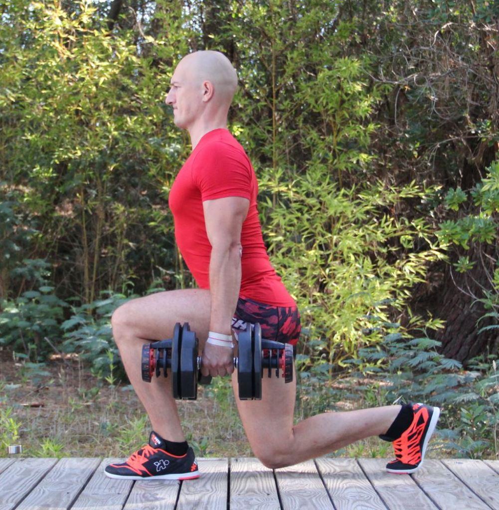 Fente arrière avec haltères (gros plan de profil)