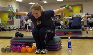 Típica chica del gimnasio que hace mil repeticiones con las pesas de colores mientras habla con las amigas sin nisiquiera sudar