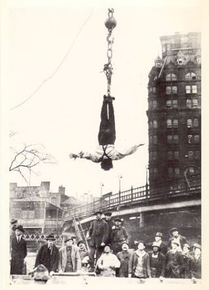 Houdini escapes from a straitjacket, suspended above his audience
