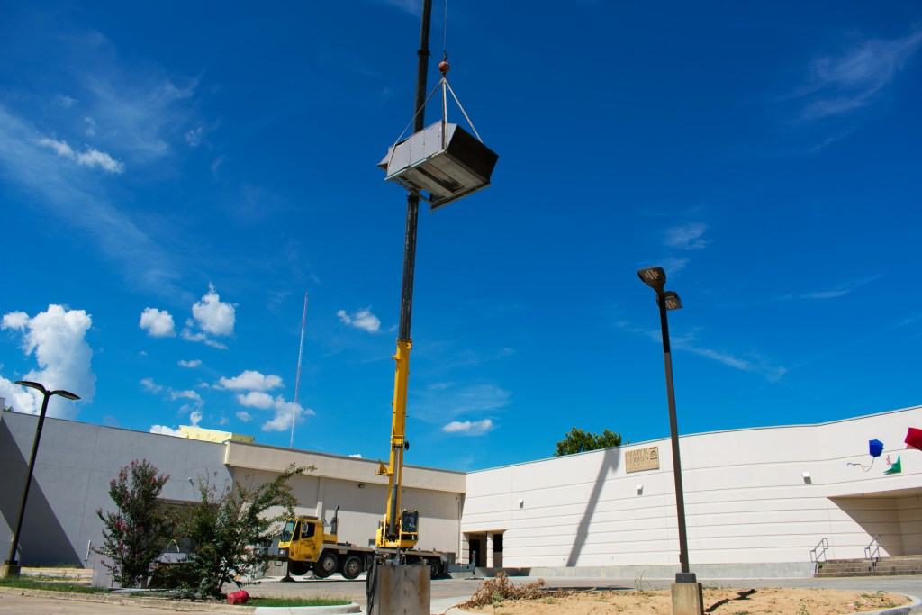 A large lowering an air conditioning unit in place on the Museum's new roof