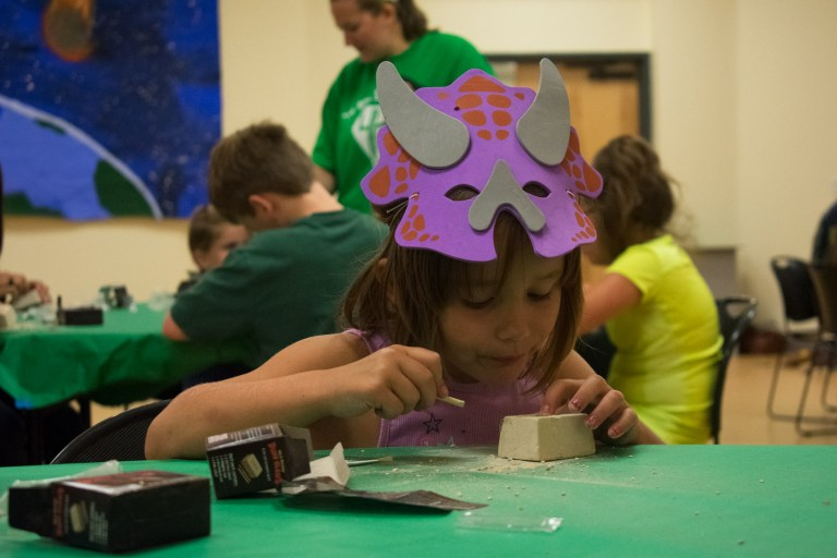 "A small girl in a dinosaur mask ""excavating"" fossils"
