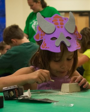 """A small girl in a dinosaur mask """"excavating"""" fossils"""