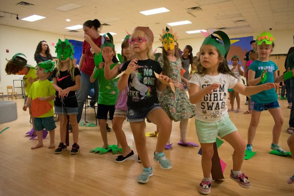 "Children dressed up as dinosaurs doing the ""dinosaur dance"""