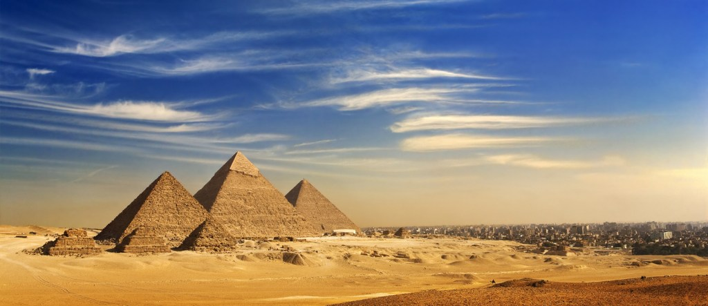 General view of pyramids and cityskape from the Giza Plateau (on front side:)