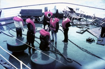 Men in lifejackets on the TEV Wahine deck next to a broken tow cable