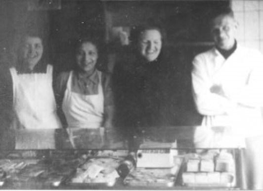 In de winkel van Bakkerij 'De Tijdgeest' in de Swammerdam-straat 12 staat het personeel achter de toonbank u vriendelijk toe te lachen. V.l.n.r. Jo Plantinga, E.C. Stekelenburg, juffrouw Wegrif en Kobus de bakker is er ook even bij komen staan.