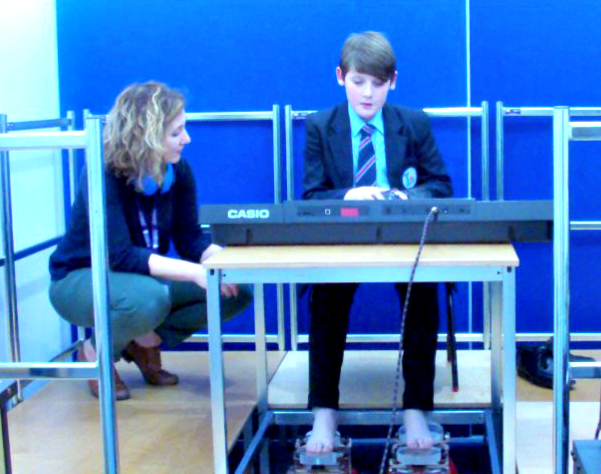 Teenage boy in blue school uniform playing an electronic keyboard and using two vibrotactile foot shakers to feel the vibrations from his playing through his feet. A woman is crouching down to his right.