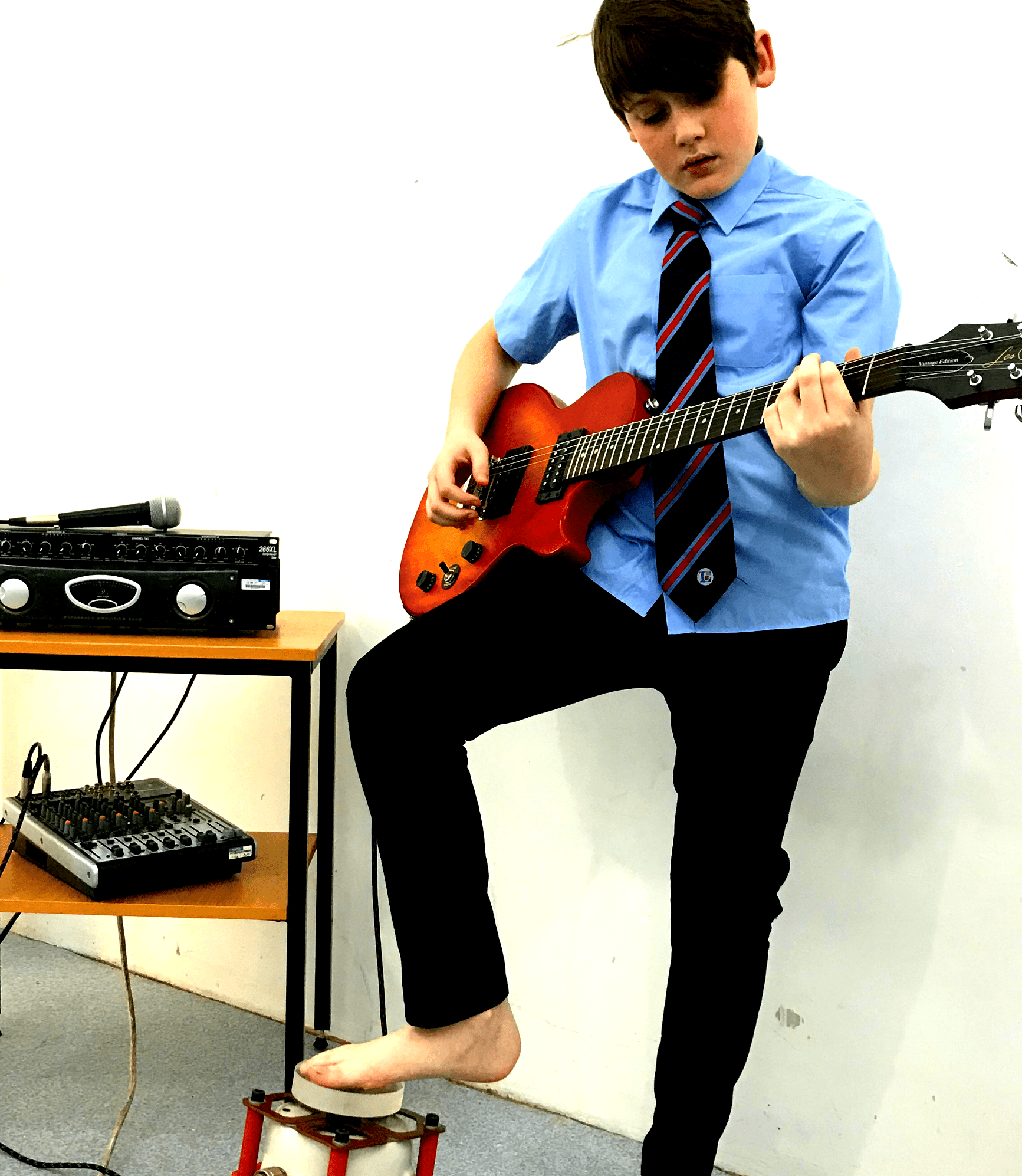 Teenage boy playing a red electric guitar. He has one bare foot placed gently on a vibrotactile foot shaker