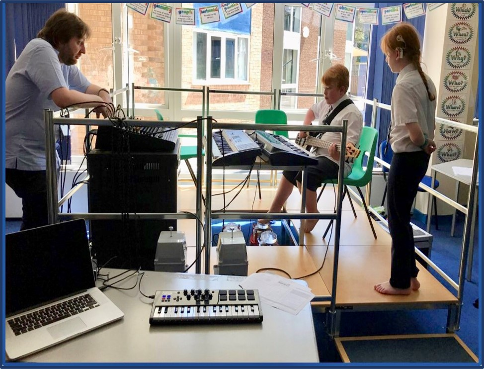 A male teacher watches a young boy around 11 years old  playing bass guitar. He is using vibrotactile equipment with his feet so that he can feel the vibrations from the bass guitar. A young girl in school uniform is watching and waiting her turn.. She is wearing a cochlear implant over her left ear.