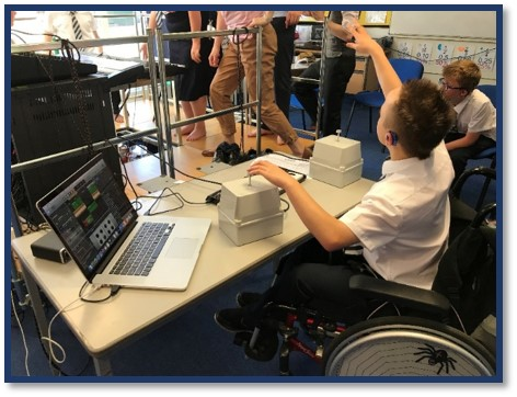 Teenage boy in school uniform in classroom, wearing hearing aid, seated in wheelchair, using vibrotactile equipment with left hand. He is attracting the attention of a teacher using sign language.