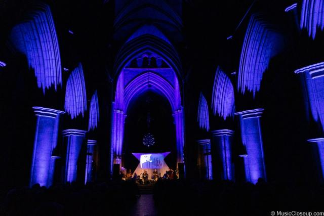 Southwark Cathedral lit up in blue with Seth Lakeman and band playing on stage in the distance