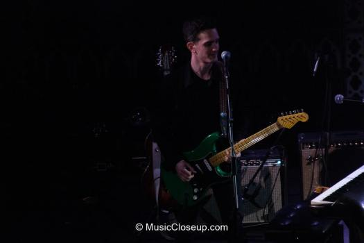 Tim Hause playing a green electric guitar