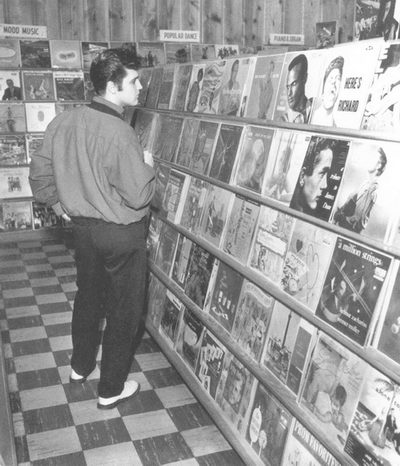 Elvis Presley , an avid record buyer, browses the hits at a Memphis record store in 1957.