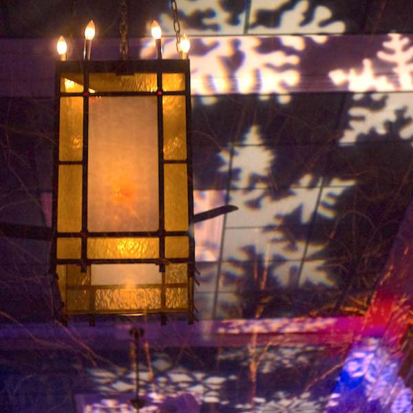 Lantern hanging from ceiling with snowflakes projected on ceiling surrounding it