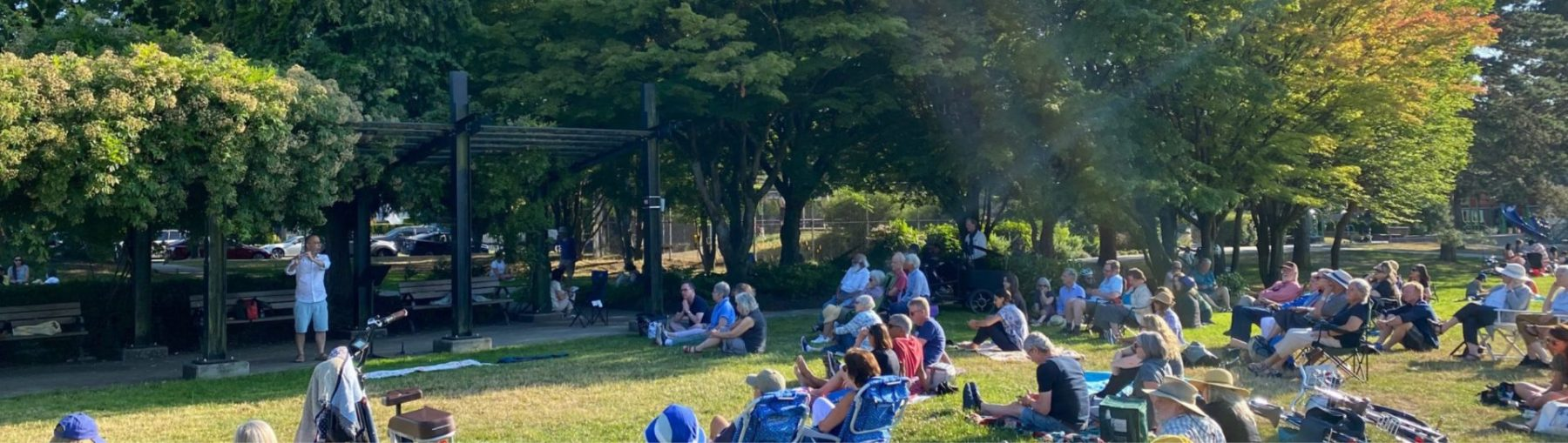 Mark Takeshi McGregor playing flute at Mount Pleasant Park in front of a live audience