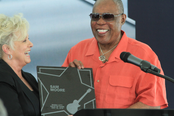 Country Music Hall of Famer Connie Smith (L) presents Sam Moore with commemorative plaque on stage.