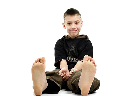 Little boy sitting barefoot, isolated on white