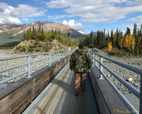 Billy walking across The McCarthy foot bridge over the kennicott River