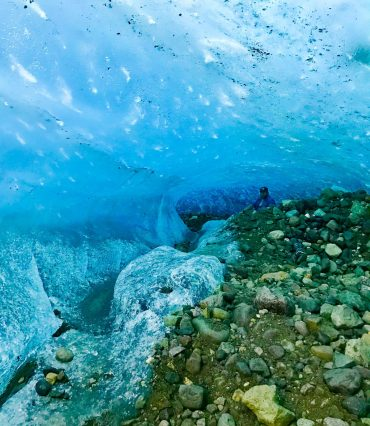 Billy sitting inside an ice cave under Root Glacier